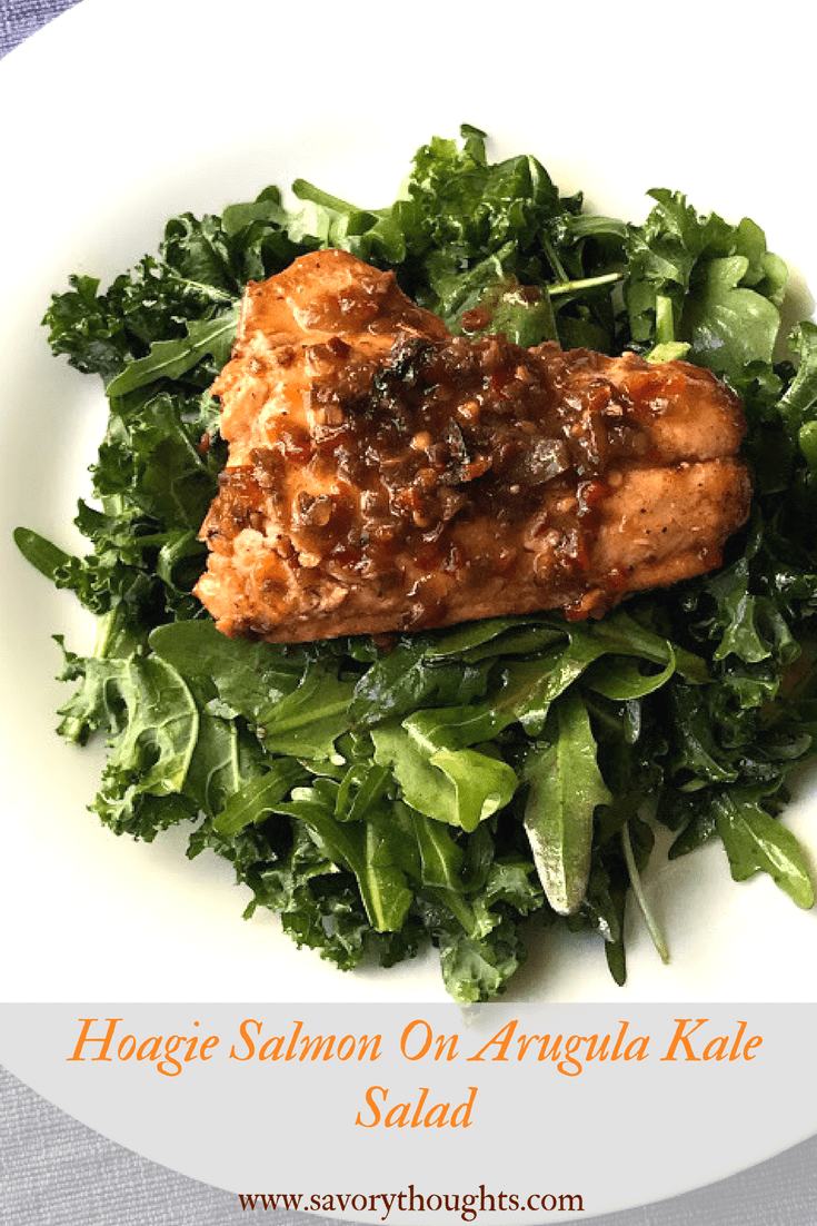 Salmon covered with Hoagie spread on a bed of arugula kale salad
