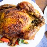 roasted chicken with curry seasoning on white plate, grilled vegetables