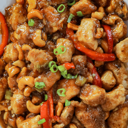 Cashew Chicken Recipe - Vertical Shot of the Cooked Recipe in a White Plate Served and Ready for Dinner
