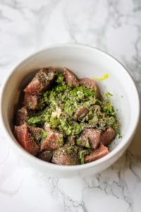 meat in a bowl with seasoning marinating