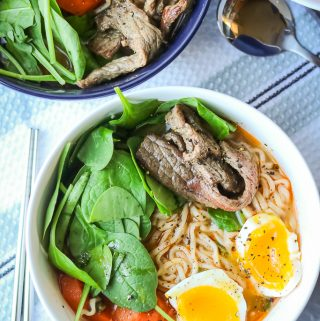 Beef, noodles, spinach, carrots, and soft boiled eggs in broth in white bowl. Full recipe at www.savorythoughts.com