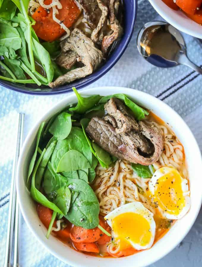 Spicy Beef Ramen Noodles. Easy beef soup recipe made with ramen noodles. Healthy and spicy. Soup made with eggs added and topped with spinach and carrots. Homemade, Authentic, and delicious. Easy and cheap to make. Best Spicy Ramen Noodle Soup. Full recipe at www.savorythoughts.com