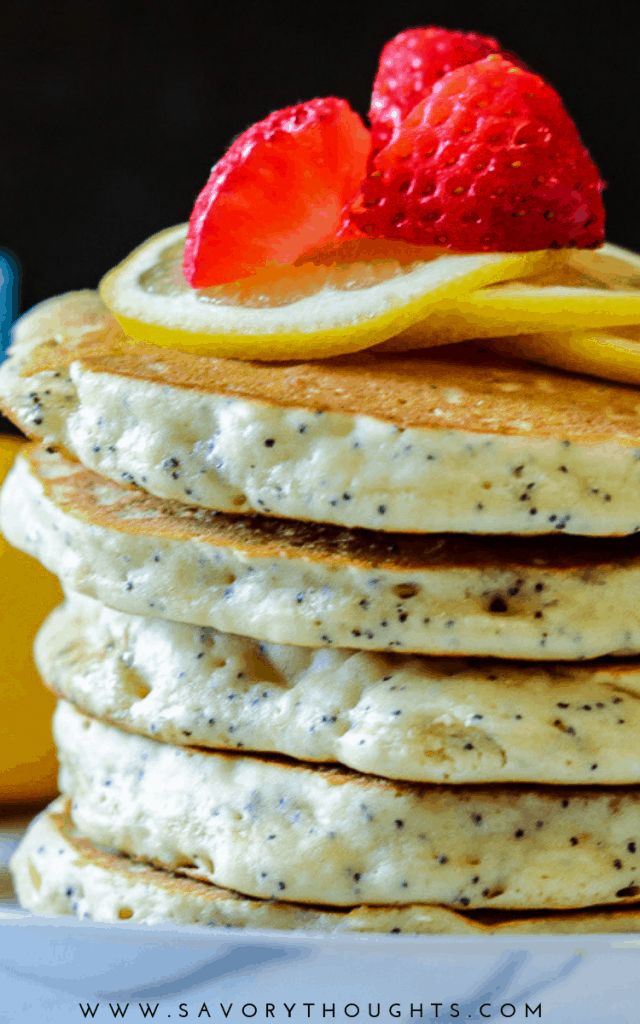 Lemon Poppyseed Pancakes stacked and topped with sliced lemon and strawberries. Serve warm with the syrup or jam of your choice. Perfect for breakfast with a cup of coffee.  Lemon Poppyseed Pancakes | Lemon Pancakes | Lemon Pancake Recipes | Poppyseed Pancakes | Pancake Recipes | Breakfast | Breakfast Pancakes | Savory Thoughts   #lemonpoppyseedpancakes #poppyseedpancakes #pancakerecipes #breakfastpancakes #breakfast