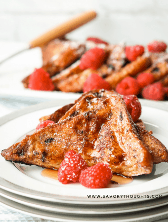 Two slices of French brioche French toast. Topped with Maple syrup and raspberries on a white plate with slices brioche French toast in the background.