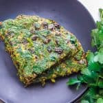 two pieces of Kuku Sabzi – Persian Herb Frittata on a black plate with fresh herbs on the side.