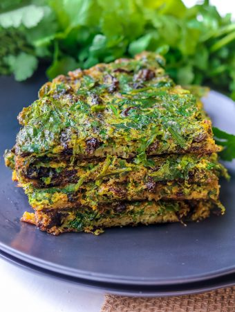 Layered Kuku Sabzi – Persian Herb on a black plate with fresh herbs in the background