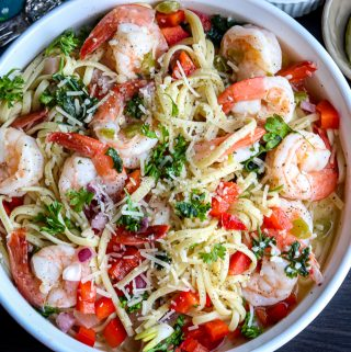 scampi pasta recipe on a white plate, topped with shrimp, herbs, tomatoes, and onions.