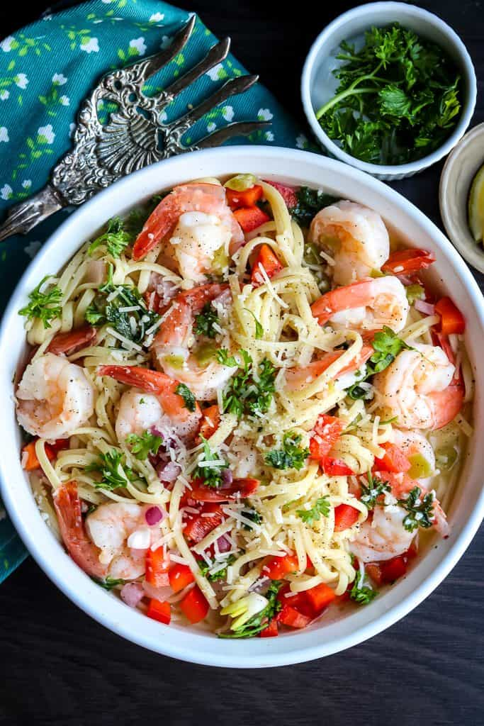 Creamy shrimp scampi on a white dish topped with fresh parsley, tomatoes, and onions.