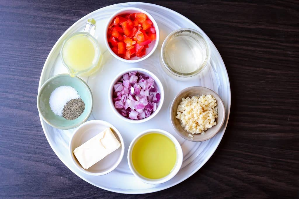Ingredients to make shrimp linguine on a white plate