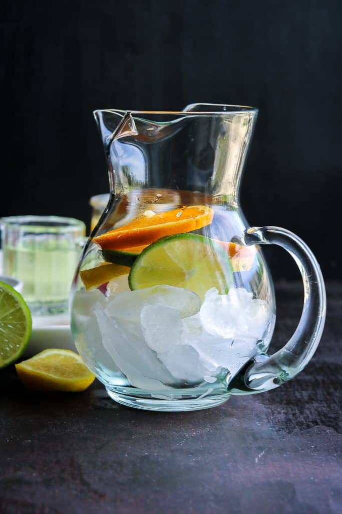 Glass pitcher showcased with ice, lemon, orange, and lime slices.