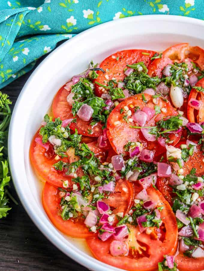Easy Marinated Tomatoes Recipe sliced on a white plate topped with fresh herbs and red onions.