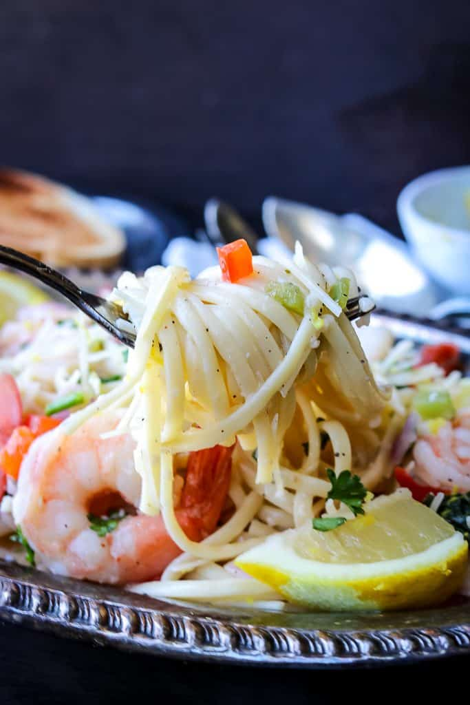 scampi pasta lifted with a fork. Plated with shrimp and lemon