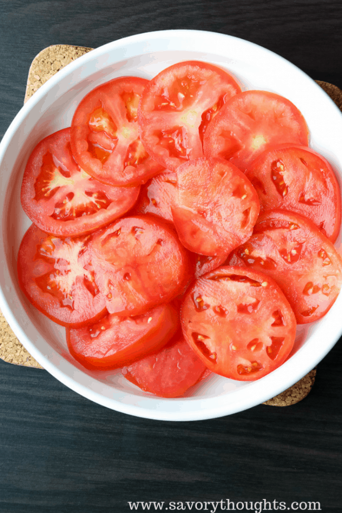 Sliced tomatoes on a white tray to prepare marinated tomatoes.
