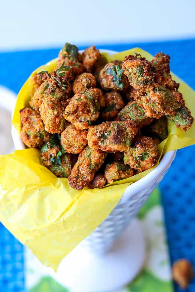 Air fryer okra bites in a white cone cup with yellow lining. Crispy Air Fryer Fried Okra recipe that's easy to make and fried to a golden crispy texture. A healthier alternative to the traditional deep-fried version. One of the best okra recipes you would want to make. #airfryerfriedokra #airfryerokra #airfriedokra #freshokra #airfryerfrozenokra #friedokrarecipe