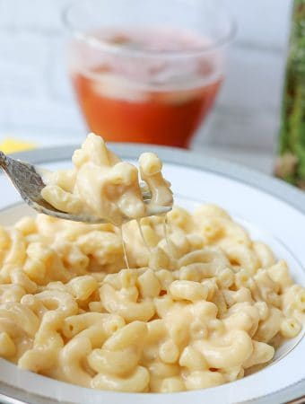 Stovetop Mac and cheese on a white plate with fork lifting the cheese macaroni with cheese dripping on the pate. Red drink in a cup in the background. This stovetop mac and cheese recipe is an outstanding, rich, creamy, and an ultra-cheesy dish! There's no need to turn to the boxed macaroni and cheese version. Prepare this creamy mac and cheese in minutes. One of the best stovetop mac and cheese.