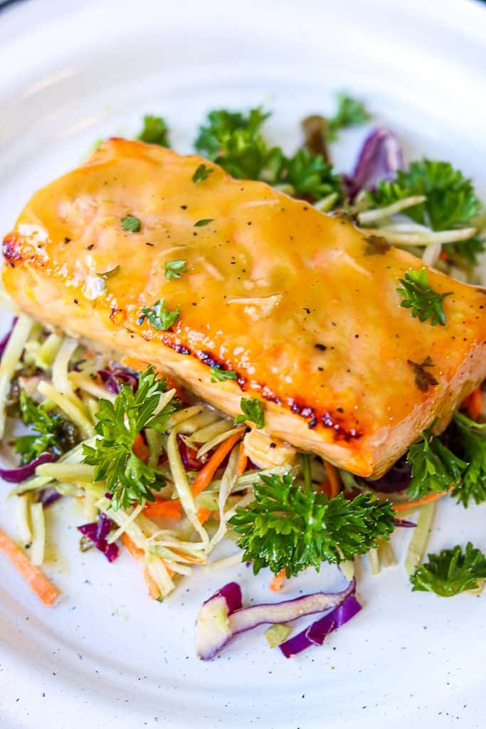 Honey Mustard Glazed Salmon on top of vegetable bed served on a white plate. Honey Mustard Glazed Salmon - Air Fryer Recipe is a quick, easy, and a healthy weeknight dinner. A hearty baked salmon recipe that's fuss-free! Baked salmon fillet made in the air fryer to perfection. A flavorful simple meal that that's ready in 10 minutes.  #air fryer #honey #mustard #dijonmustard #recipes #paleo #honeymustardglaze #healthy #lemon