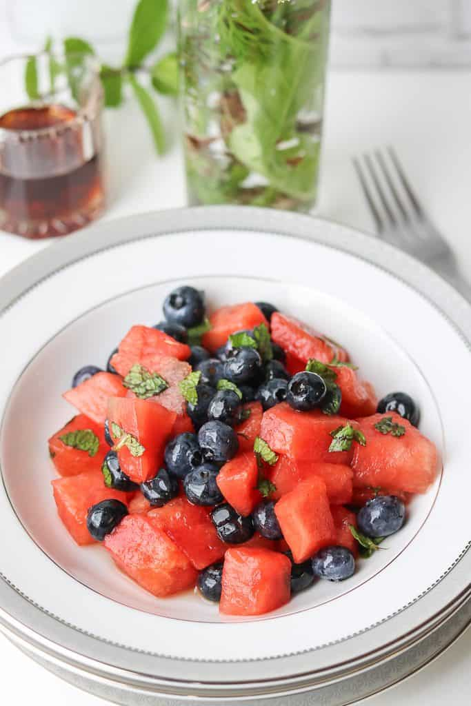 This sweet Watermelon Blueberry Salad combination is exactly what you need as a healthy snack on a light day. Cubed fresh watermelon tossed with blueberries, and maple syrup and fresh lemon juice. Then, topped with chopped mint leaves to create a light and refreshing side dish that will please your guests. #watermelonblueberry #salad