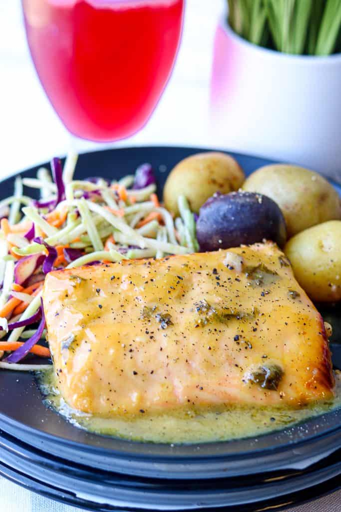 air fryer honey glazed salmon on a black plate with mixed vegetables and potatoes