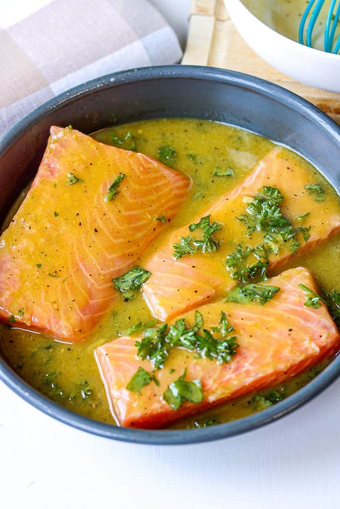 salmon in a baking dish topped wth honey mustard glaze and fresh chopped parsley
