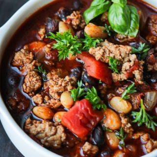 Chili in a white plate topped with fresh herbs and tomatoes