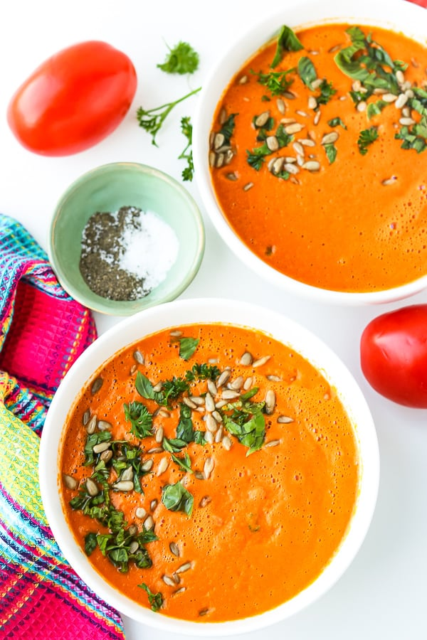 Two bowls of Tomato Carrot Soup topped with chopped fresh herbs and pumpkin seeds