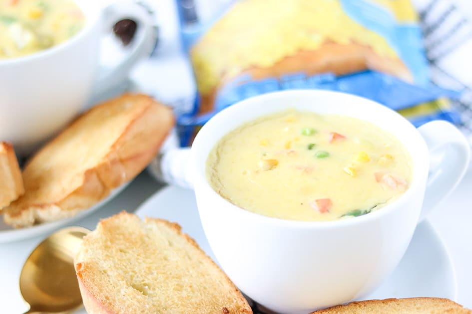 Vegetarian corn chowder in white cup with bread