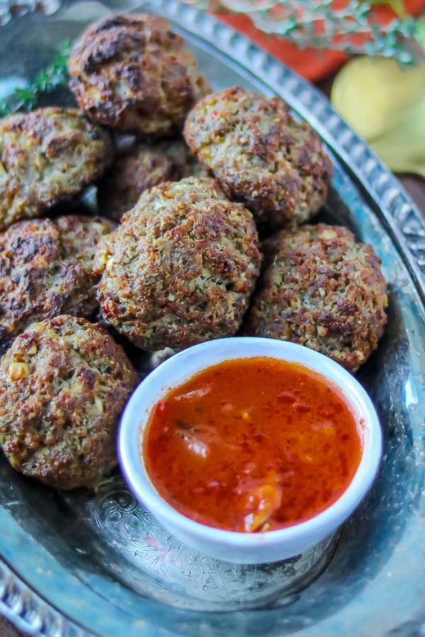 Haitian meatballs in silver platter with sauce