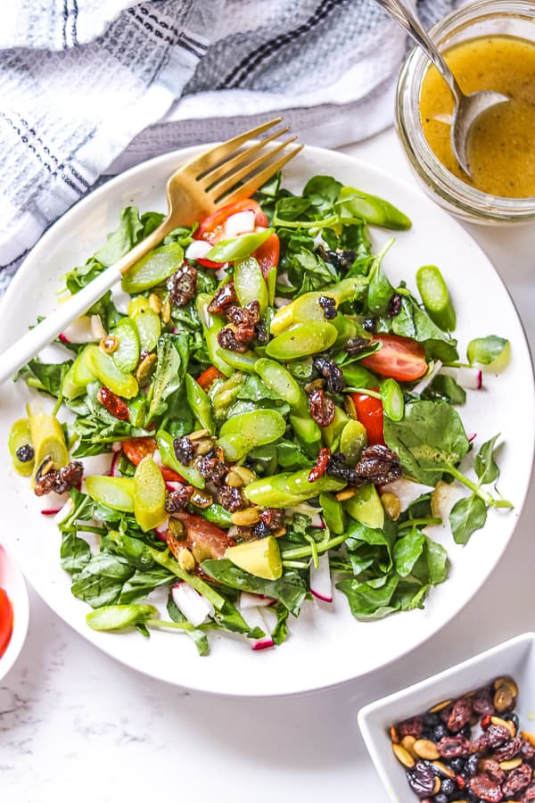 Asparagus salad with cranberry vinaigrette on white plate