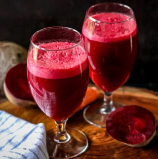 Beets Carrots Apple Juice Recipe in glasses on wooden cutting board -Healthy