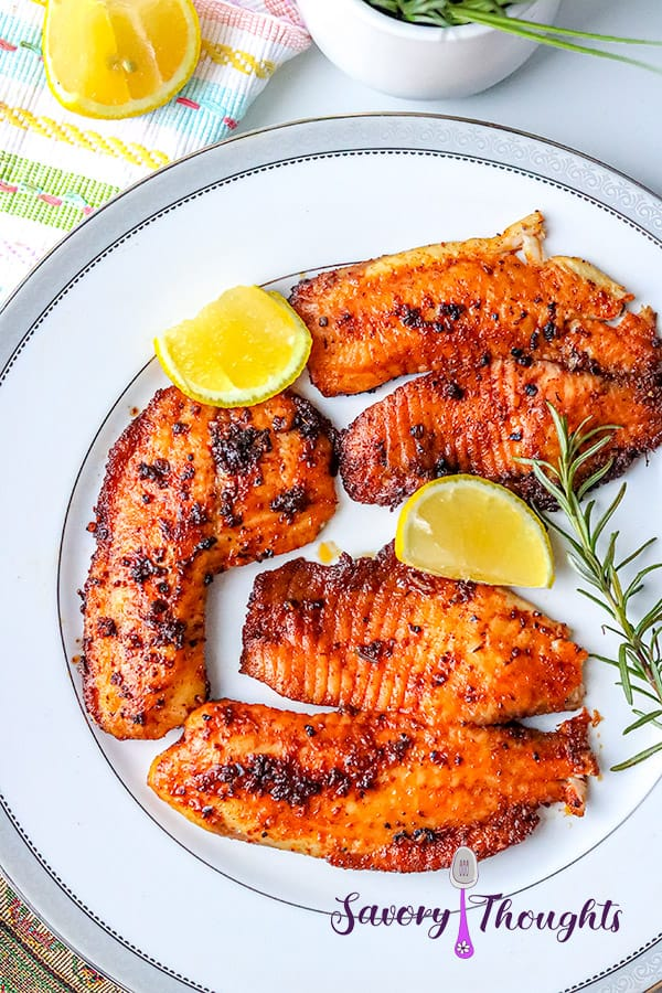 fish on white plate with lemon wedges and rosemary sprig.