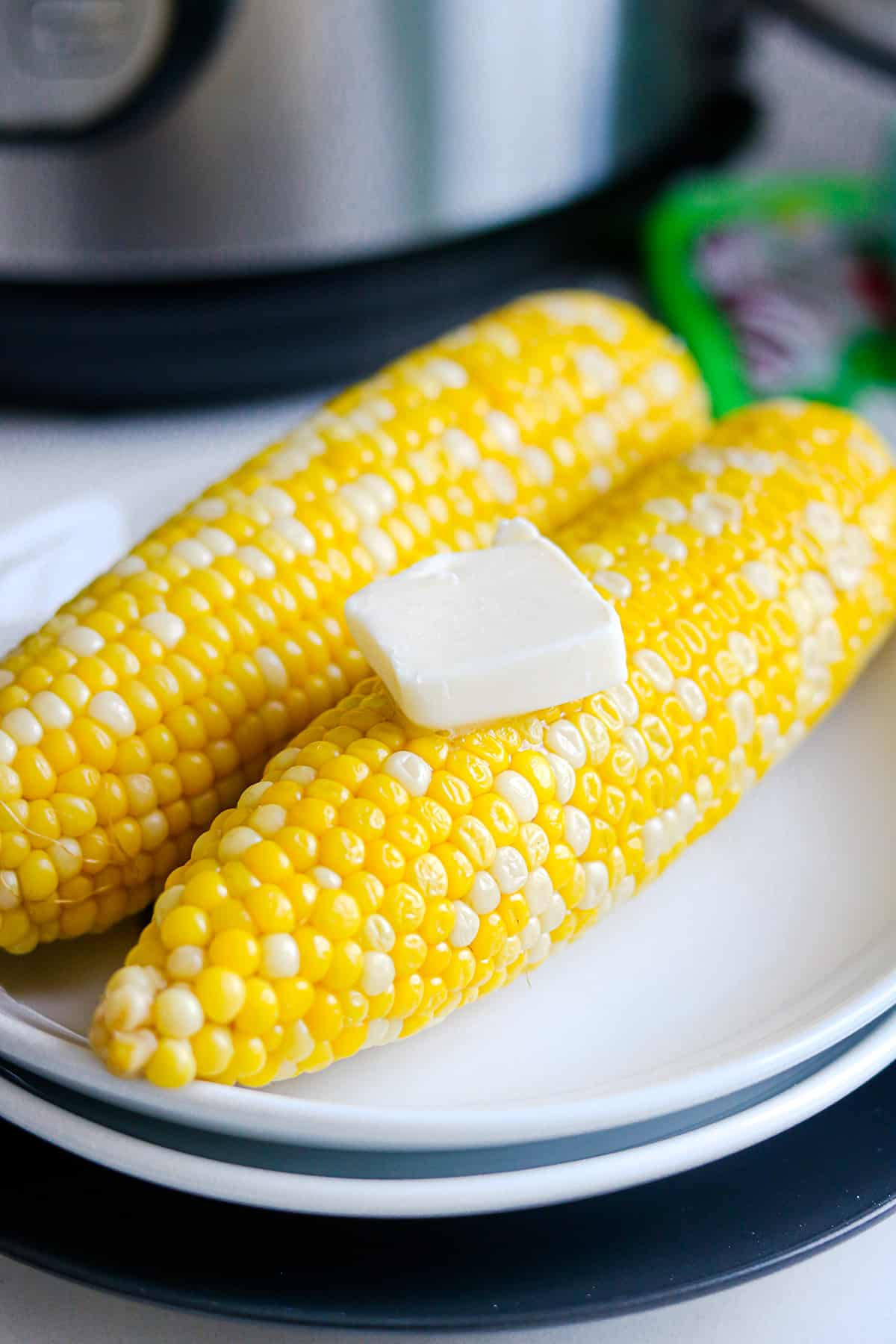 Corn on white plate with butter on top