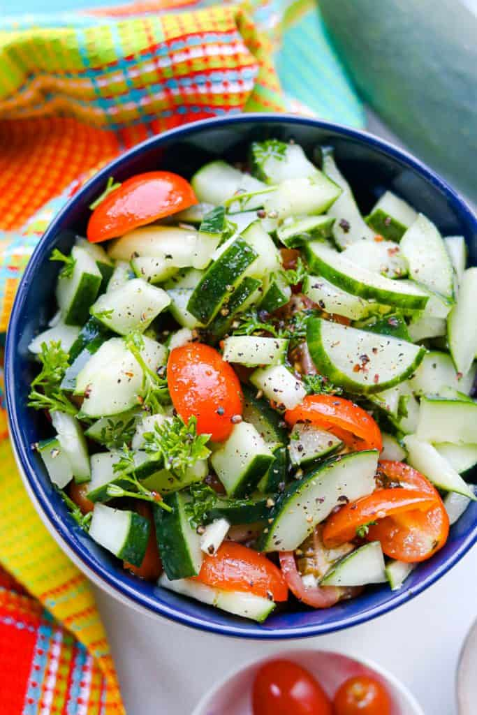 Cucumber Salad In dark blue plate with colorful tablecloth, cherry tomatoes, and cucumber