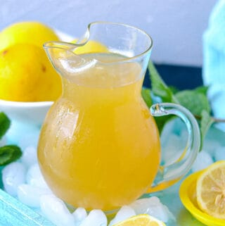 Lemonade in pitcher over ice on a blue tray