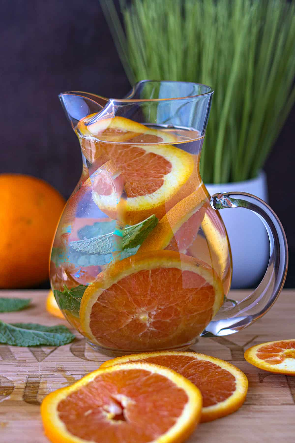 Orange Infused Water In pitcher with orange slices on cutting board