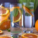 orange infused water in glasses and pitcher with orange slices on cutting board