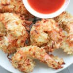 Shrimp coated with coconut flakes air fried on white plate