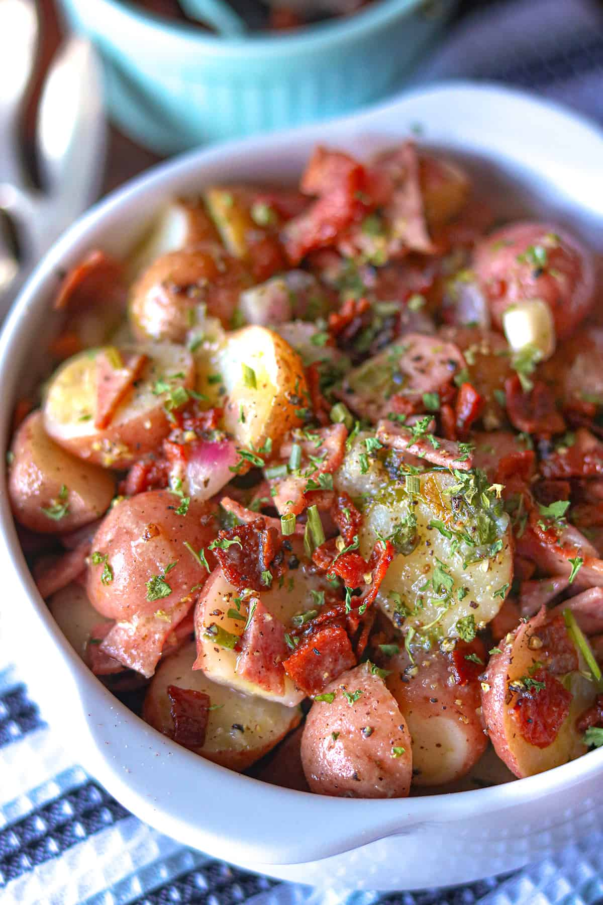 German potato salad topped with herbs and bacon