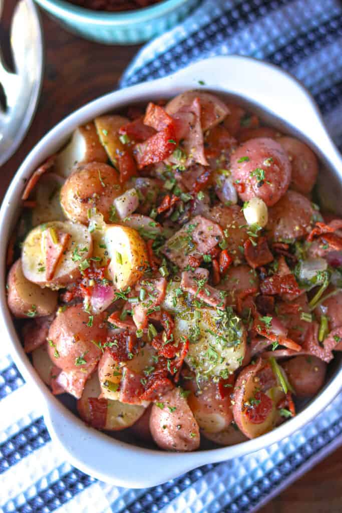 potato salad on a wooden cutting board topped with herbs