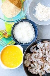 shrimp in a bowl, eggs, coconut flakes, flour and seasoning in separate bowls