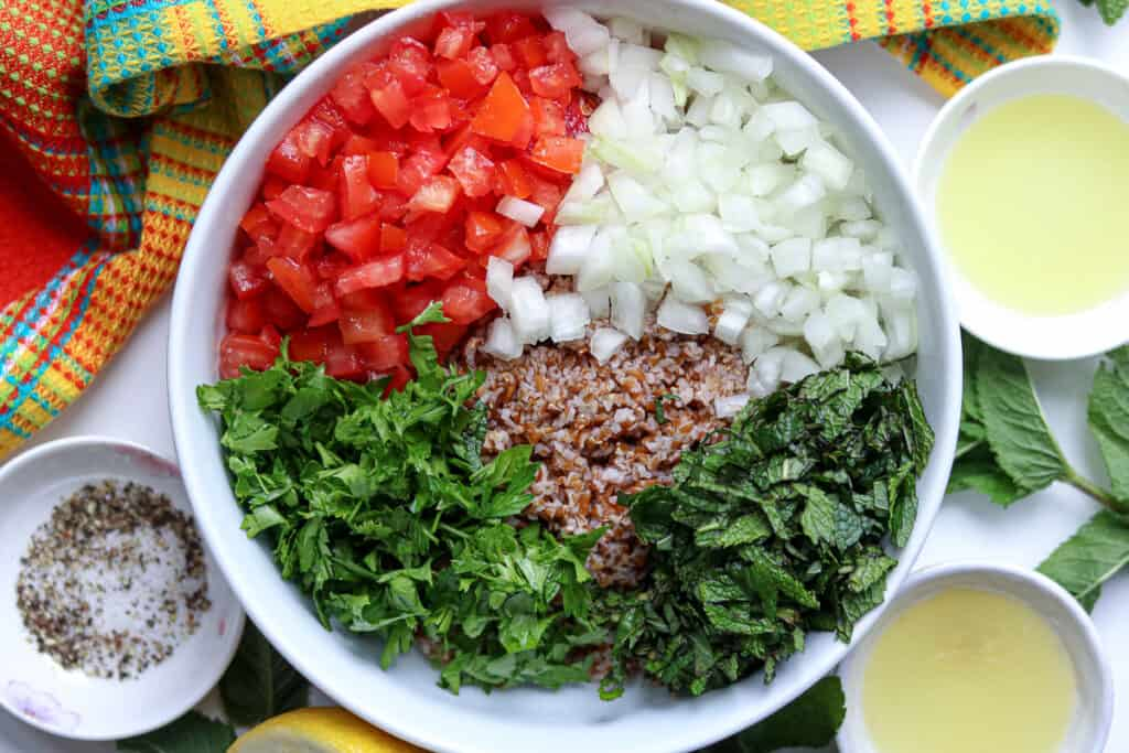 Tomatoes, onions, mint, bulgur, parsley in large bowl