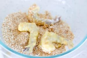 Shrimp being coated in panko breadcrumbs and seasoning.
