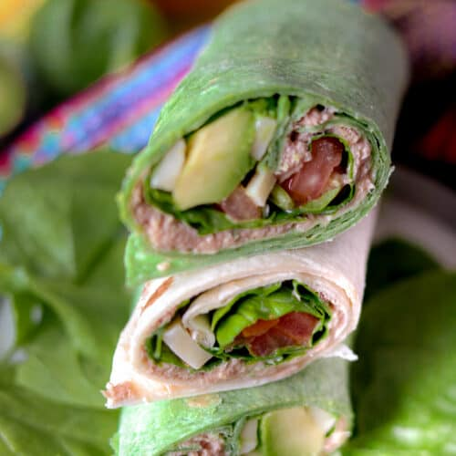 Tuna Wraps stacked on top of each other on a bed of spinach leaves