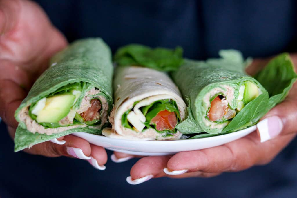 pair of two hands holding tuna wraps on a plate.