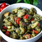 Delicious Pesto Chicken Gnocchi in white bowl on wooden spoon board