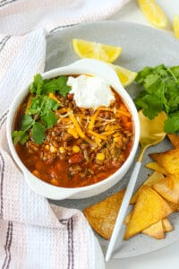 Turkey taco soup in white plate topped with fresh herbs and sour cream