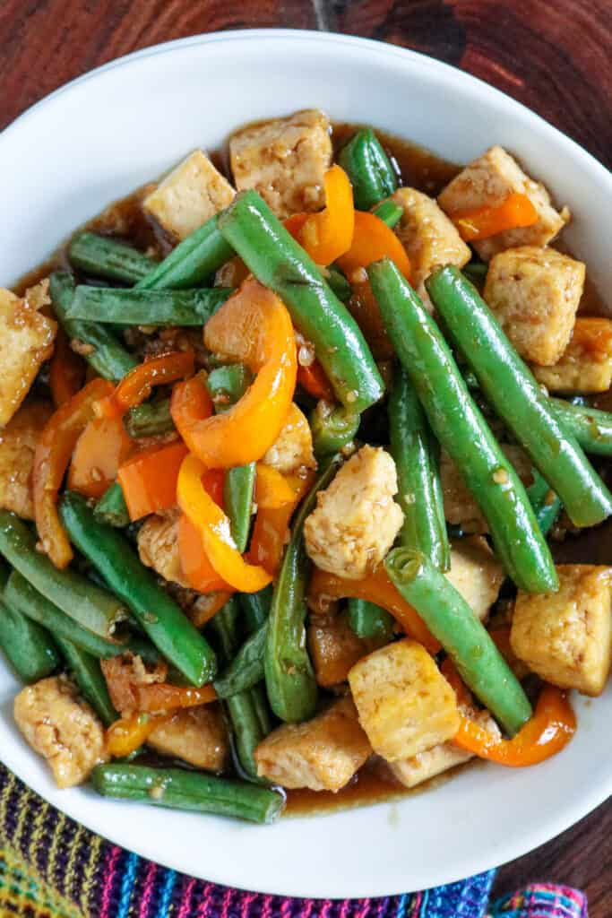 Tofu and green beans in white plate