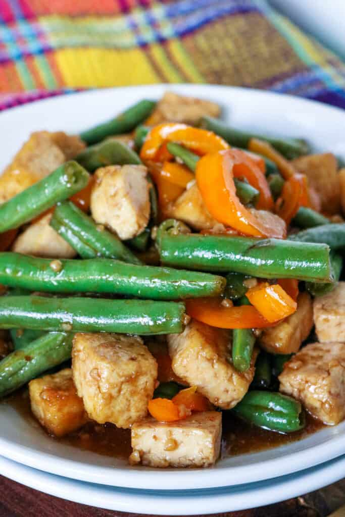 Tofu and green beans with peppers on a white plate