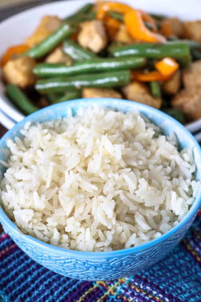 White rice in a blue plate with green beans tofu in the background