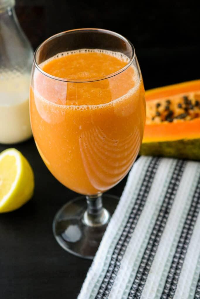 Juice in glass on blackboard with papaya in the background, including milk, lemon juice