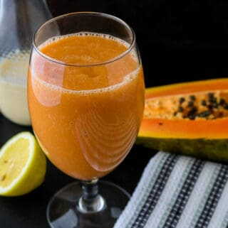 Papaya Juice in glass on blackboard with lemon and papaya in the background with almond milk